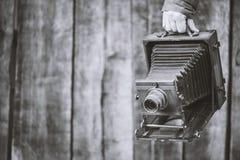 Cámara retra del formato grande, pulgadas 5x7 El fotógrafo sostiene la cámara vieja del estudio Efecto monocromático, espacio de  fotos de archivo libres de regalías