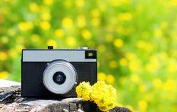 Cámara retra del vintage con las flores amarillas sobre bokeh soleado del verano Imagenes de archivo