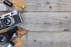 Cámara retra, lentes y película negativa en backgroun de madera de la tabla Fotos de archivo libres de regalías