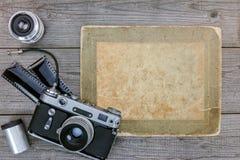 Cámara retra, película negativa, lentes en fondo de madera de la tabla Imagen de archivo