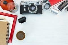 Cámara retra, pote del café, marco rojo de la foto y cuaderno en blanco Imágenes de archivo libres de regalías
