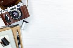Cámara retra vieja en la cubierta, el cuaderno, la pluma, y la película de rollo de cuero Imagen de archivo libre de regalías