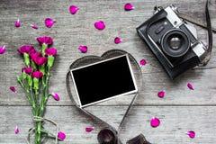 Cámara retra y marco en blanco de la foto en película en forma de corazón con las flores Foto de archivo libre de regalías