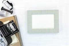 Cámara retra y marco gris de la foto en la visión plana superficial de madera Imagen de archivo