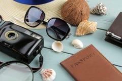 Cámara, vidrios, pasaporte y sombrero del concepto del viaje en una tabla de madera azul Relajación holidays imagenes de archivo