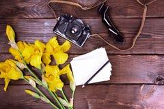 Cámara vieja de la película y un ramo de iris amarillos Fotos de archivo libres de regalías