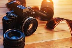 Cámara vieja de la película y un rollo en de la madera Fotos de archivo libres de regalías