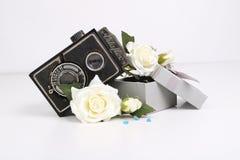 Cámara y flores y caja viejas fotografía de archivo libre de regalías