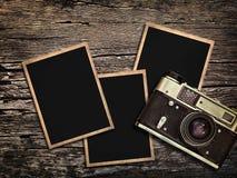 Cámara y fotos viejas del vintage en un fondo de madera Fotos de archivo libres de regalías