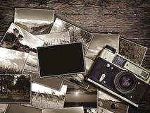 Cámara y fotos viejas del vintage en un fondo de madera Foto de archivo