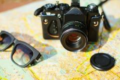 cámara y gafas de sol en el mapa turístico Imagenes de archivo