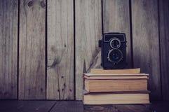 Cámara y una pila de libros Fotografía de archivo libre de regalías