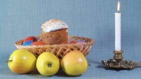 Cámaras del viaje, arreglo de Pascua, Pascua en la cesta de madera con los huevos pintados y Apple, cerca de la vela blanca adent metrajes