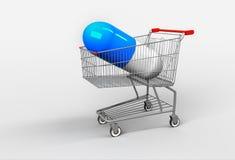Cápsula azul grande com as medicinas que encontram-se no carrinho de compras Conceito Fotografia de Stock