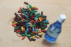 Cápsula de Ayurvedic com garrafa de água azul fotos de stock