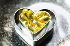 Cápsula del aceite de pescado en la caja doble de la forma del corazón en la más pequeña en el bl Foto de archivo