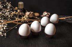Cápsula del papel acanalado con los huevos blancos y las ramitas secas Imagen de archivo