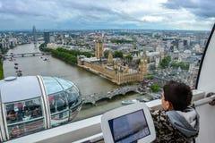 A cápsula do olho de Londres - menino novo que olha para fora a janela na skyline Fotos de Stock