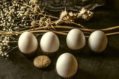 Cápsula do papel ondulado de Brown com ovos brancos em um fundo preto Fotos de Stock