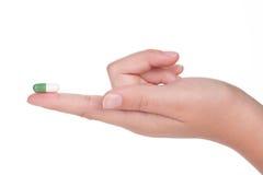 Cápsula médica verde en una mano femenina, aislada foto de archivo libre de regalías