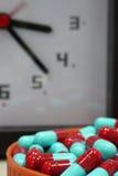 Cápsula roja y azul con el fondo del reloj Imágenes de archivo libres de regalías