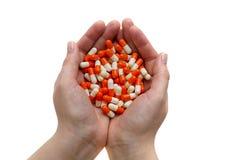 Cápsulas anaranjadas en las manos de la muchacha Imágenes de archivo libres de regalías