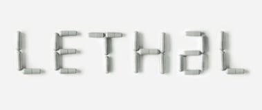 Cápsulas blancas de las píldoras en la forma de la palabra mortal Concepto de la vida aislado foto de archivo
