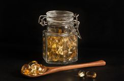 Cápsulas da prímula de noite em um frasco de vidro e em uma colher de madeira fotografia de stock royalty free