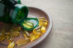 Cápsulas de gelatina amarelas do óleo de semente da prímula de noite e bot verde imagens de stock royalty free