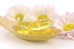 Cápsulas de gelatina macias do suplemento dietético no tom claro morno Fotografia de Stock