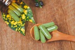 Cápsulas de la medicina herbaria en cuchara de madera Imagen de archivo