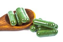Cápsulas de la medicina herbaria en cuchara de madera Fotografía de archivo