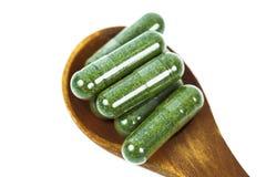 Cápsulas de la medicina herbaria en cuchara de madera Fotos de archivo