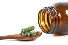 Cápsulas de la medicina herbaria en cuchara de madera Foto de archivo