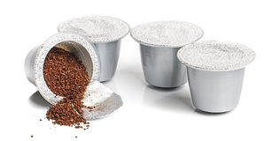 Cápsulas del café de Nespresso aisladas en el fondo blanco Imagen de archivo
