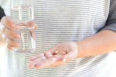 cápsulas disponível com vidro da água Foto de Stock