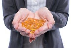 Cápsulas do óleo de peixes na mão fêmea Fotografia de Stock
