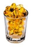 Cápsulas do óleo de peixes no vidro no fundo branco Fotografia de Stock Royalty Free