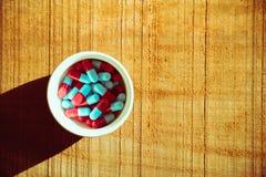 Cápsulas do comprimido no fundo de madeira Fotografia de Stock