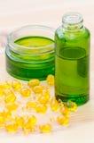 Cápsulas do ouro com óleos essenciais para garrafas da cara e do verde na madeira imagem de stock