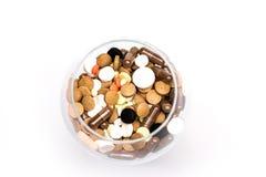 Cápsulas e tabuletas médicas dentro do vidro Fotografia de Stock