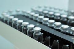 Cápsulas estéril para la inyección Botellas en la línea de embotellamiento de la planta farmacéutica Máquina después de comprobar Fotos de archivo libres de regalías