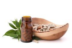 Cápsulas herbarias de la droga en botella de cristal marrón. Medicina alternativa Imágenes de archivo libres de regalías