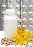 Cápsulas líquidas amarelas e placas prateadas das medicinas perto de uma garrafa Foto de Stock Royalty Free