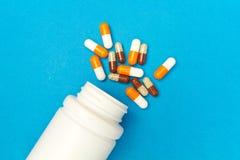 cápsulas & x28; pills& x29; foram derramados de uma garrafa branca em um fundo azul Fundo médico, molde fotografia de stock