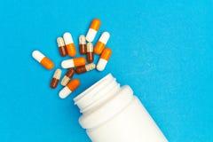 cápsulas & x28; pills& x29; foram derramados de uma garrafa branca em um fundo azul Fundo médico, molde imagem de stock royalty free