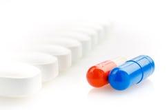 Cápsulas rojas, azules y píldoras blancas Imágenes de archivo libres de regalías