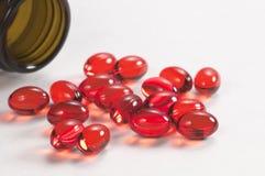 Cápsulas rojas cerca de la caja Imagen de archivo