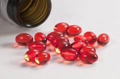 Cápsulas rojas cerca de la caja Imagen de archivo libre de regalías