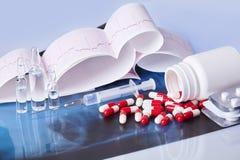 Cápsulas, tabletas, ampollas y jeringuilla dispersadas en la tabla con el cardiograma foto de archivo